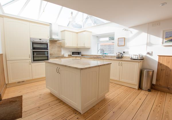 Kitchen cooking with a glass vaulted ceiling star gazing from indoors